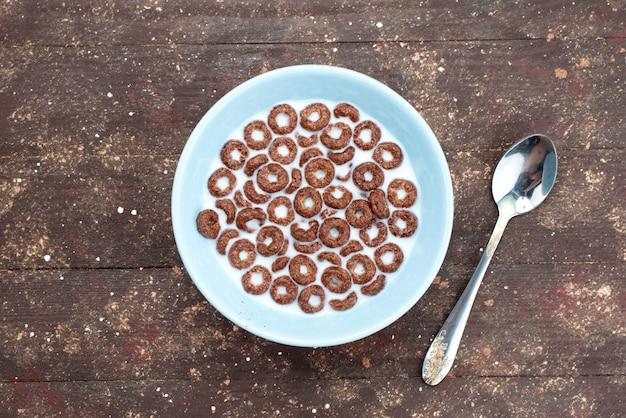 Vista superior de cereales de chocolate con leche dentro del plato azul y junto con una cuchara en marrón