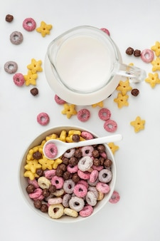 Vista superior de cereales de desayuno multicolores en diferentes formas con leche