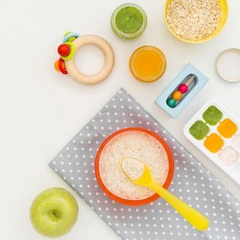 Vista superior de cereales con leche para bebé y juguetes