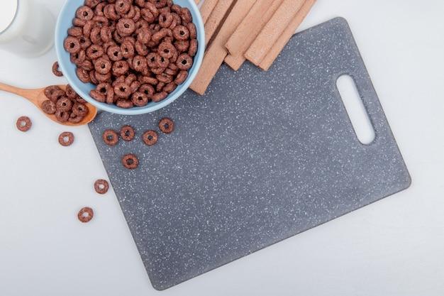Vista superior de cereales en un tazón y una cuchara de madera con leche y galletas en la tabla de cortar sobre fondo blanco.