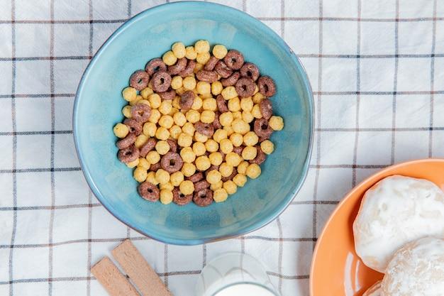Vista superior de cereales en un tazón con galletas de leche de pan de jengibre sobre tela escocesa