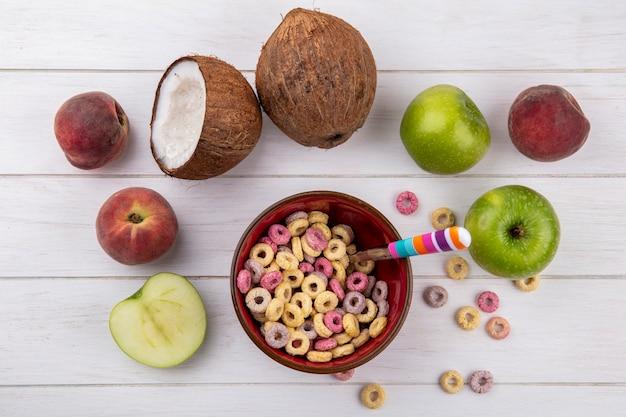 Vista superior de cereales en tazón rojo con cuchara con coco manzanas melocotones en blanco