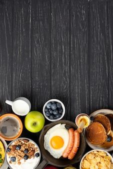 Vista superior de cereales y yogurt con salchichas y huevo para el desayuno.