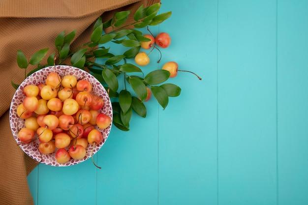 Vista superior de cereza blanca en un plato con ramas de hojas y una toalla marrón sobre una superficie turquesa