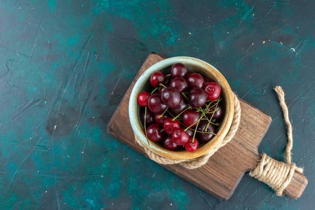 Vista superior de cerezas ácidas frescas dentro del tazón con cuerdas en color oscuro, fruta fresca y amarga