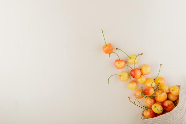Vista superior de cerezas amarillas derramándose de saco en el lado derecho y mesa blanca