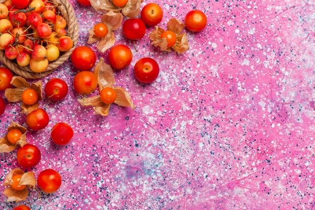 Vista superior cerezas dulces frescas con ciruelas en el escritorio de color rosa claro.