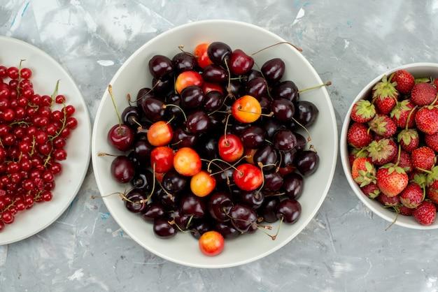 Una vista superior de cerezas y fresas con arándanos dentro de la placa blanca.