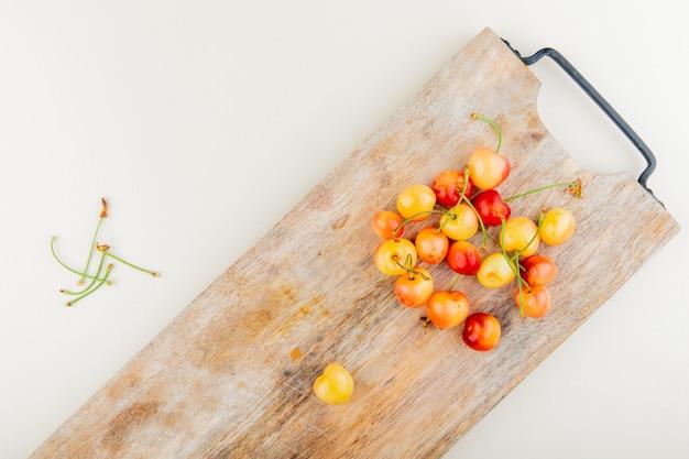 Vista superior de cerezas en tabla de cortar con tallos en superficie blanca