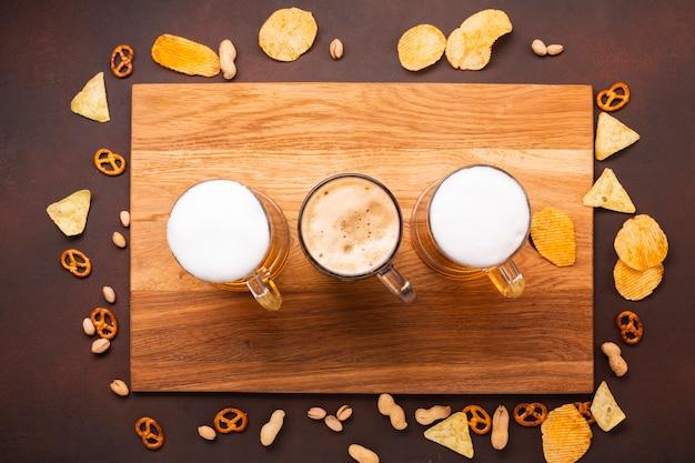 Vista superior de cerveza con aperitivos en tabla de cortar