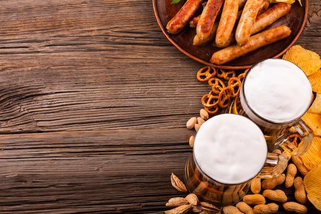 Vista superior de cerveza con comida en la mesa de madera