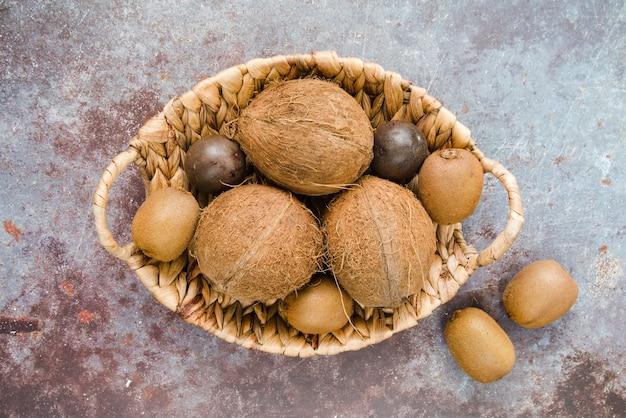 Vista superior cesta llena de coco y kiwi