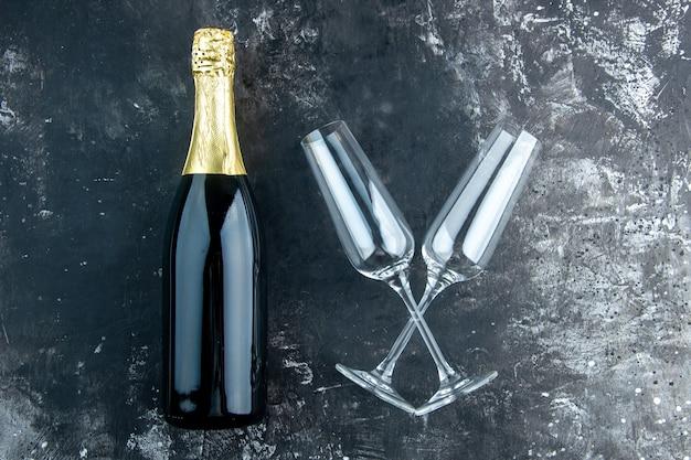 Vista superior champán cruzó copas de champán en mesa oscura