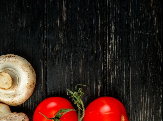 Vista superior de champiñones blancos frescos y tomates en madera oscura con espacio de copia