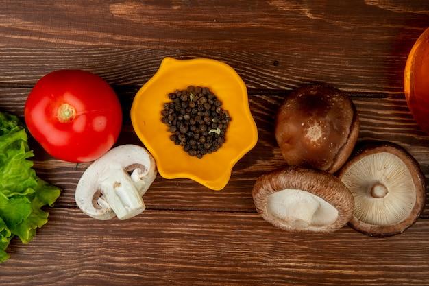 Vista superior de champiñones frescos y granos de pimienta negra con tomate en madera rústica