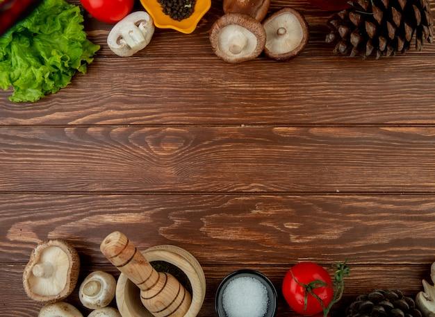 Vista superior de champiñones frescos con granos de pimienta negra, tomates frescos, mortero de madera con hierbas secas, sal y conos en madera rústica con espacio de copia