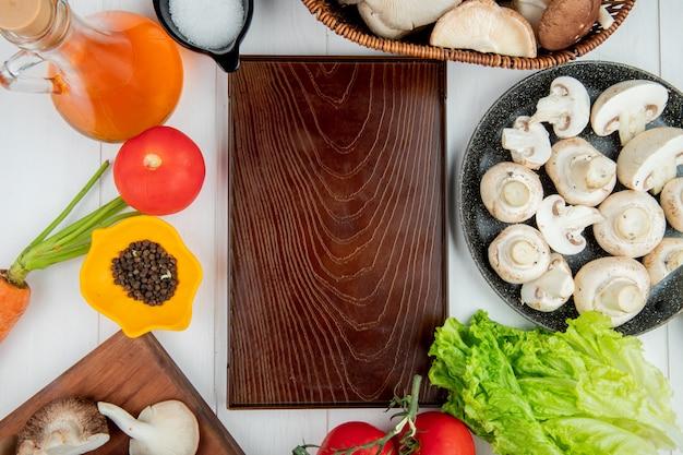 Vista superior de champiñones frescos en un plato de tomates botella de aceite de oliva, sal y granos de pimienta dispuestos alrededor de un tablero de madera en blanco