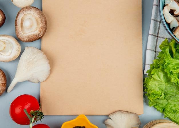 Vista superior de champiñones frescos con tomate lechuga dispuestos alrededor de un cuaderno de bocetos en azul claro