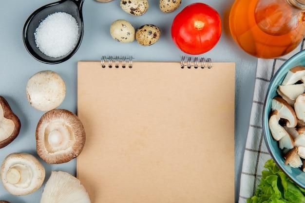 Vista superior de champiñones frescos con tomates, huevos de codorniz y sal dispuestos alrededor de un cuaderno de bocetos en azul claro