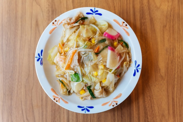 Vista superior de champon ramen con carne de cerdo, camarones, cebolleta, brotes, zanahoria, col, maíz y kamaboko.