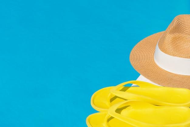 Vista superior de chanclas de color amarillo brillante y un sombrero de paja que se encuentran en la acera de la piscina contra un fondo de agua azul.