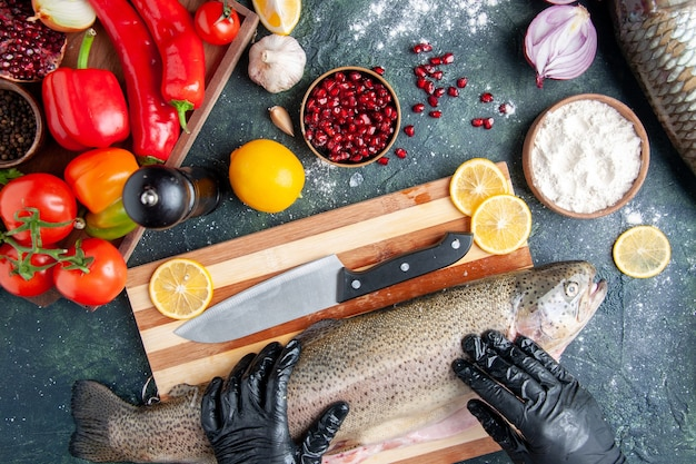 Vista superior del chef con guantes negros sosteniendo pescado crudo en tablero de madera molinillo de pimienta harina tazón de granada semillas en un tazón en la mesa de la cocina