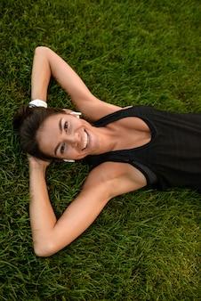 Vista superior de una chica feliz fitness en colocación de auriculares