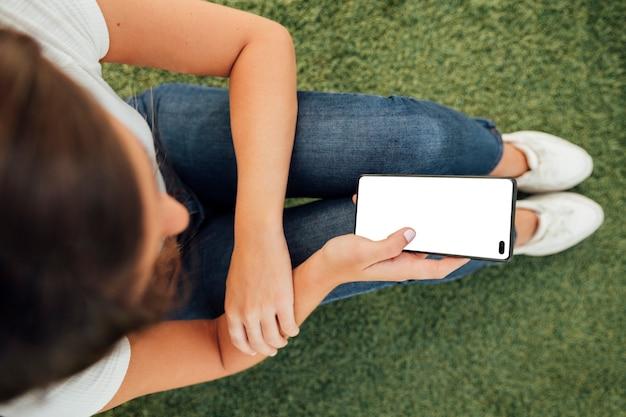 Vista superior chica sosteniendo teléfono con maqueta