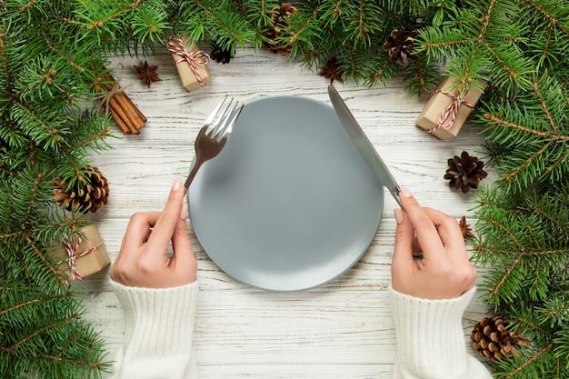 Vista superior chica tiene tenedor y cuchillo en la mano y está lista para comer. plato vacío redondo de cerámica en la mesa de madera. concepto de plato de cena navideña con decoración navideña