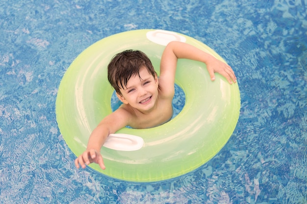 Vista superior chico en piscina con flotador