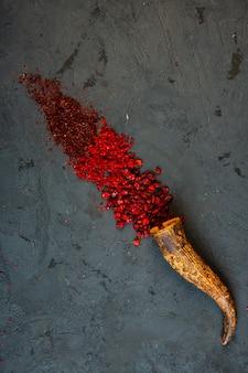 Vista superior de chile rojo y polvo de zumaque en negro