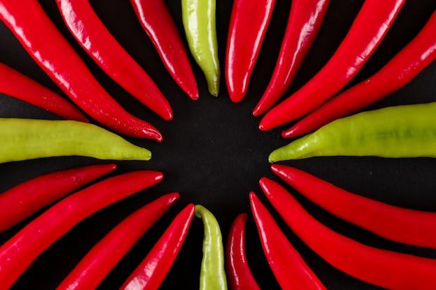 Vista superior de chiles rojos y verdes sobre superficie negra