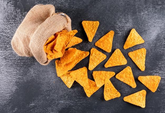 Vista superior chips en bolsa de lino en piedra negra horizontal
