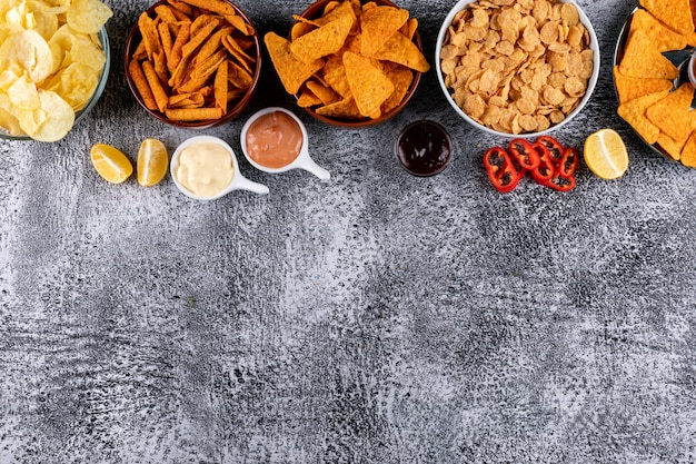 Vista superior chips en cuencos con sause pimienta de limón y copia espacio en piedra blanca horizontal