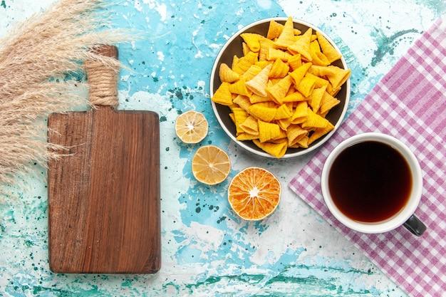 Vista superior de chips de galleta con taza de té en la superficie azul