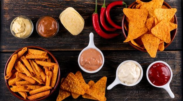 Vista superior chips con guindilla y salsas en tazones en madera marrón horizontal