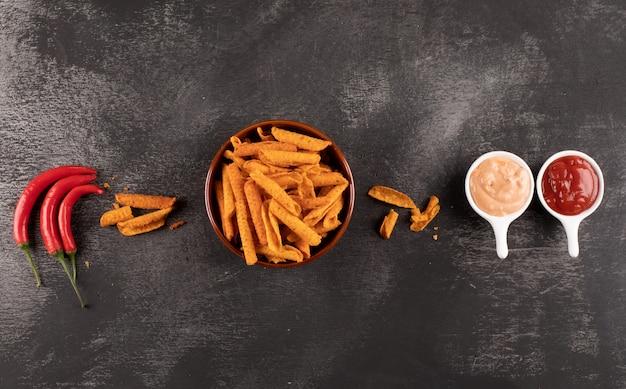 Vista superior chips con guindilla y salsas en tazones de piedra negra