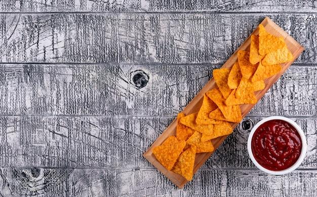 Vista superior chips y salsa en tazones y copia espacio a la izquierda en horizontal de madera blanca