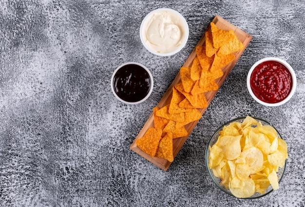 Vista superior chips y salsas en tazones y copia espacio a la izquierda en piedra blanca