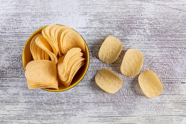 Vista superior de chips en un tazón en blanco horizontal