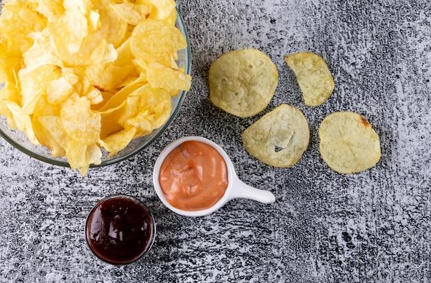 Vista superior chips en un tazón con salsas en piedra blanca horizontal