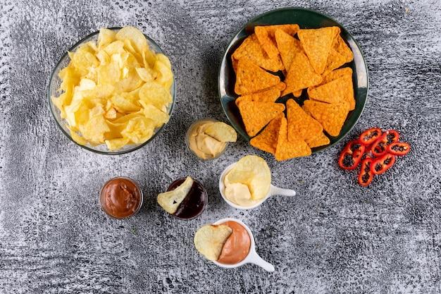 Vista superior chips en un tazón con salsas y pimienta en piedra blanca horizontal