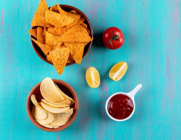 Vista superior chips en un tazón con tomate limón y salsa en horizontal azul