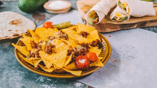 Vista superior de chips de tortilla mexicana de nachos en un tazón con tacos mexicanos en tabla de cortar