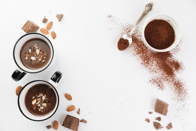 Vista superior chocolate caliente con frutos secos y cacao en polvo