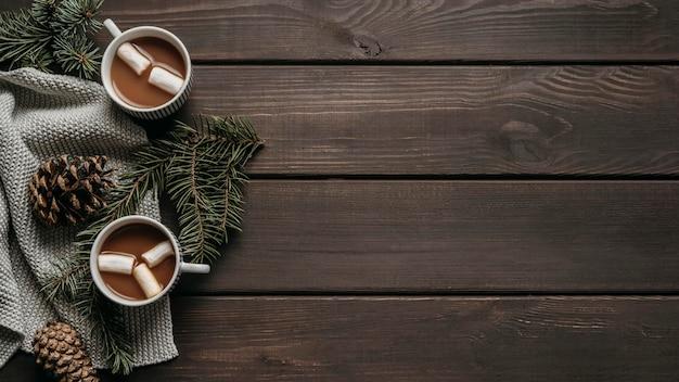 Vista superior de chocolate caliente con ramas de pino, conos y espacio de copia