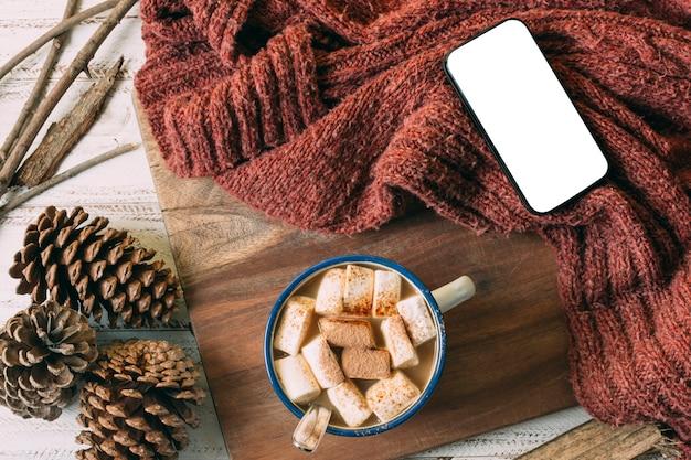 Vista superior de chocolate caliente con teléfono simulado