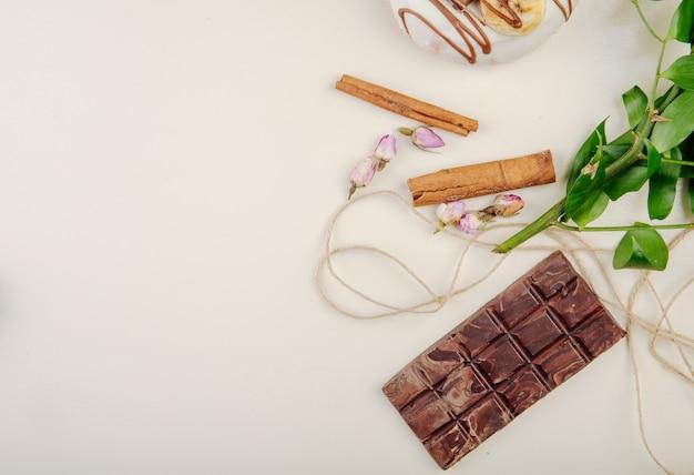Vista superior de chocolate y canela con hojas en blanco con espacio de copia