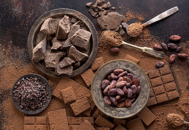 Vista superior de chocolate con plato de granos de cacao