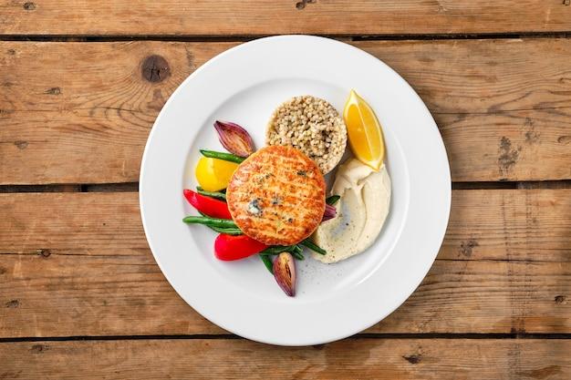 Vista superior de chuleta de salmón con verduras asadas y trigo sarraceno verde